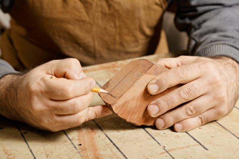 Handwerkerhände, die auf hölzernem Billet skizzieren lizenzfreies stockfoto