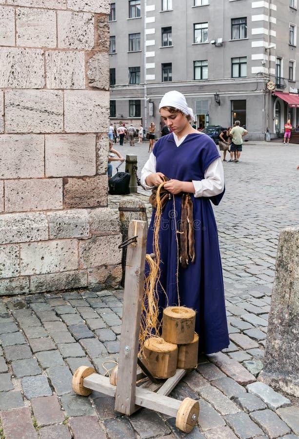 Handwerkerin, die am mittelalterlichen Handwerksmarkt arbeitet stockbilder