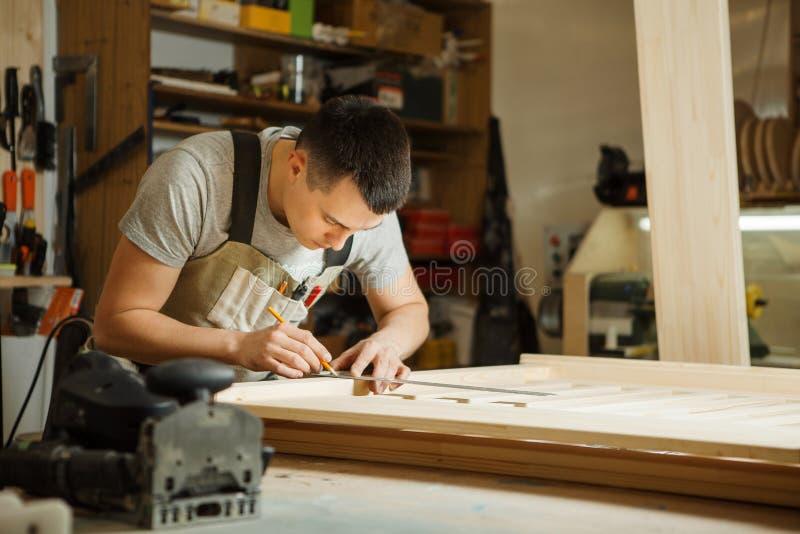 Handwerkermaßabstand zwischen hölzernen Planken mithilfe des Machthabers stockfotografie