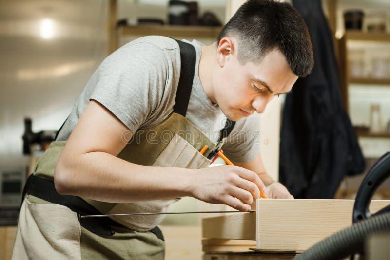 Handwerkermaßabstand zwischen hölzernen Planken mithilfe des Machthabers stockbilder
