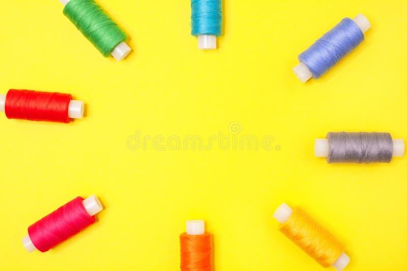 Handwerkshintergrund Stellen Sie von den mehrfarbigen Spulen des Fadenformrahmens auf gelbem Hintergrund mit Kopienraum ein stockfoto