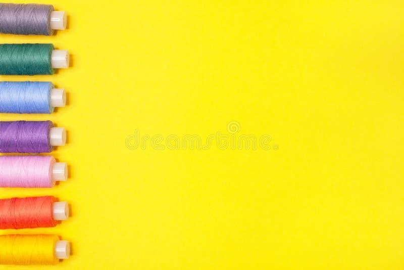 Handwerkshintergrund Stellen Sie von den mehrfarbigen Spulen des Fadens auf gelbem Hintergrund mit Kopienraum ein Zubehör für Näh lizenzfreie stockbilder