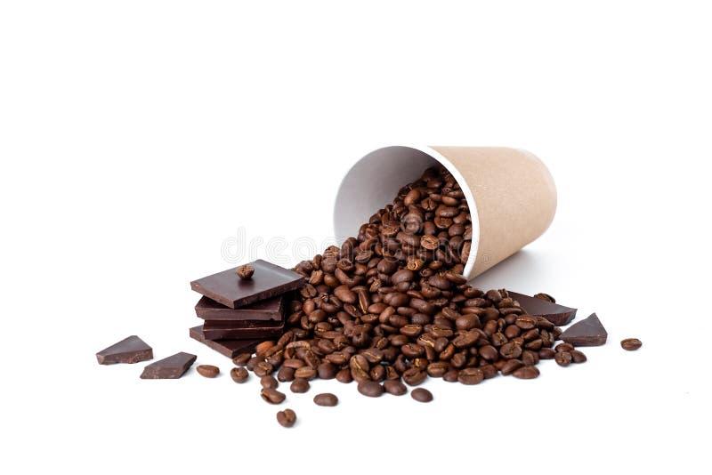 HandwerksKaffeetasse voll Kaffeebohnen mit Schokolade auf weißem Hintergrund stockbilder