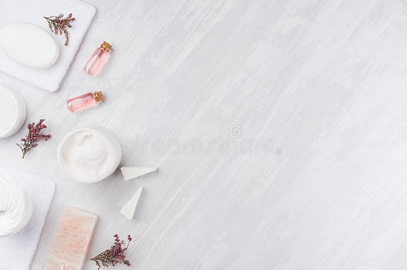 Handwerksnaturkosmetik - weiße Creme, Seife, Lehm, rosafarbenes Öl, Tuch, rosa Blumen und Badzubehör auf Weiß des weichen Lichtes stockfotos