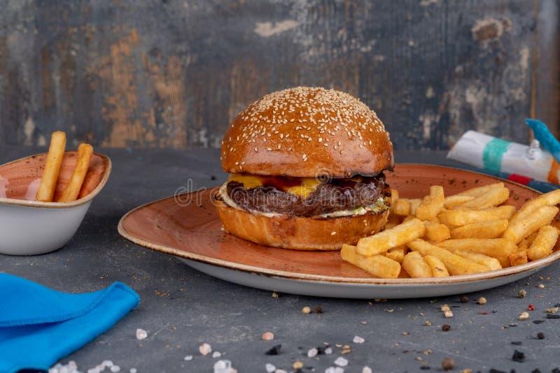 Handwerksrindfleischburger mit Brötchen und Pommes-Frites des indischen Sesams auf Steinhintergrund lizenzfreie stockfotografie