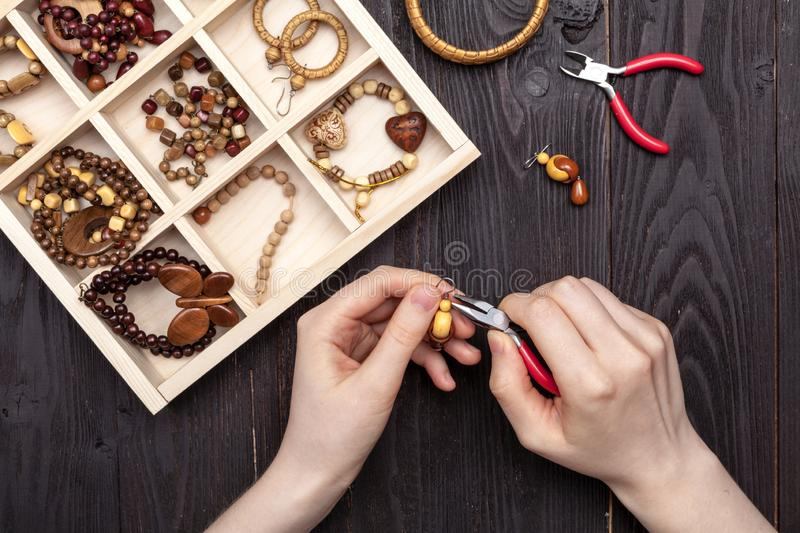 Handwork at home, the girl makes jewelry hands on the table royalty free stock image