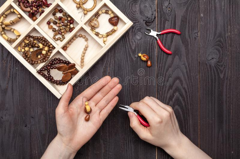 Handwork at home, the girl makes jewelry hands on the table royalty free stock photos