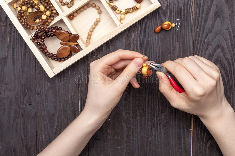 Handwork at home, the girl makes jewelry hands on the table royalty free stock images