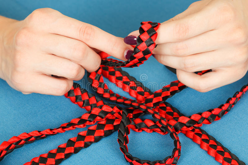 Handwork. weaving belt of satin ribbons. On a blue background stock image