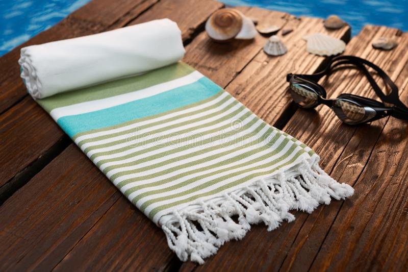 Handwoven blue hammam Turkish cotton towel on dark wooden bridge. Surrounded by shells royalty free stock image