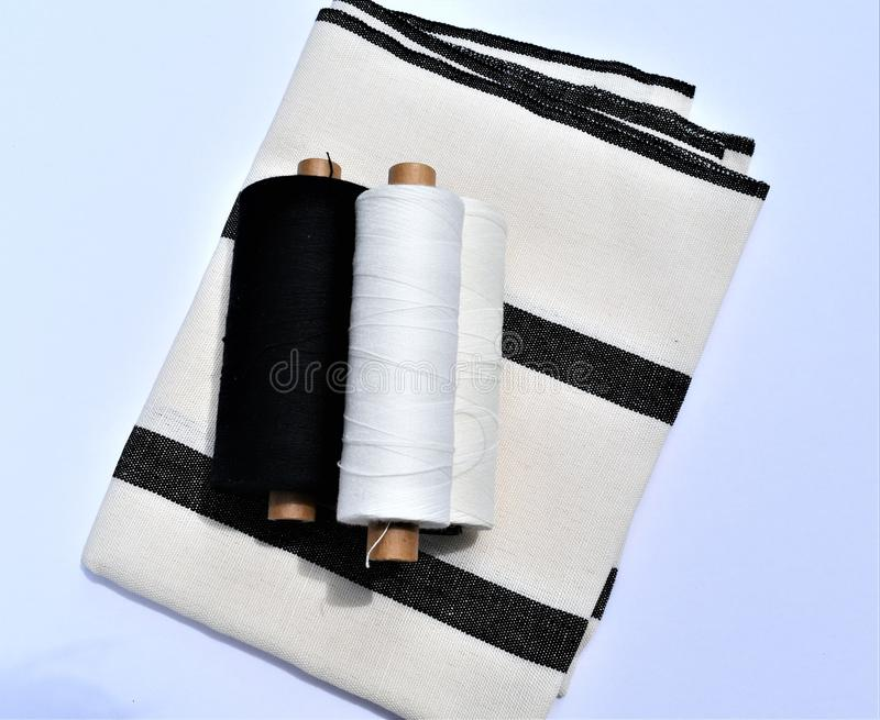Weaving. Handwoven cotton and linen towel with yarns used to make the towel. Textiles. Black and off-white striped handwoven towel. Yarns used to make the stock photography