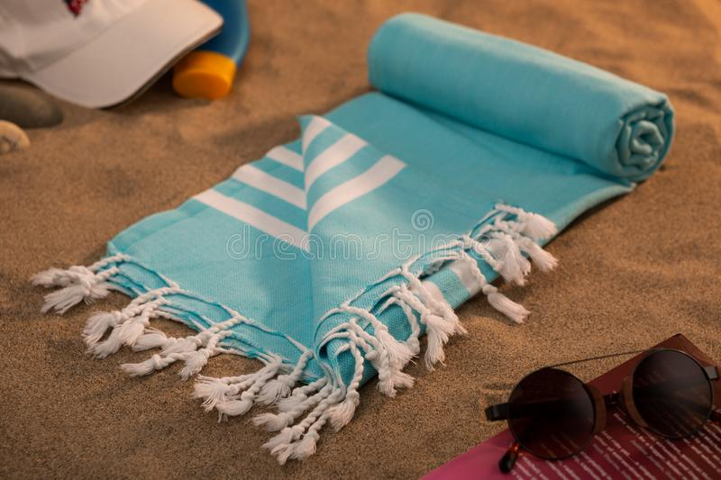 Handwoven hammam Turkish cotton towel. On beach, with book, sunglasses and baseball hat on the side stock photos