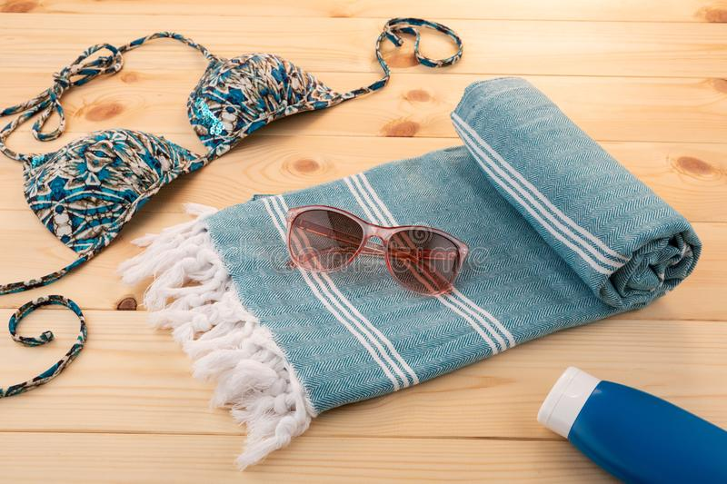 Blue Handwoven hammam Turkish cotton towel. Handwoven hammam Turkish cotton towel on light wooden background with bikini and sunglasses on the side stock photography