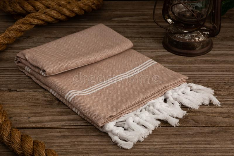 Handwoven hammam Turkish cotton towel on rustic wooden background. Dark beige Handwoven hammam Turkish cotton towel on rustic wooden background with thick rope stock photo