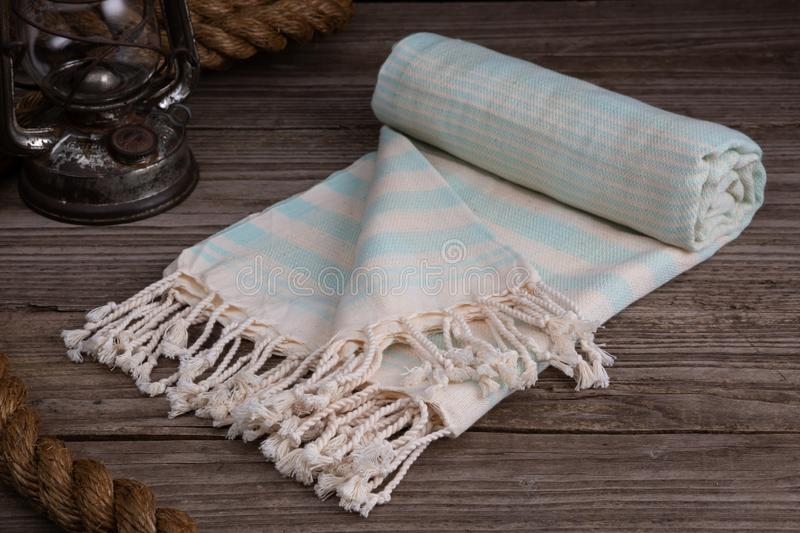 Handwoven hammam Turkish cotton towel on rustic wooden background. Light blue Handwoven hammam Turkish cotton towel on rustic wooden background with thick rope royalty free stock photo