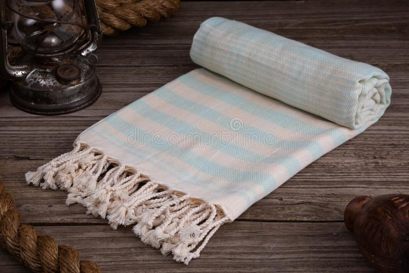 Handwoven hammam Turkish cotton towel on rustic wooden background. Light blue Handwoven hammam Turkish cotton towel on rustic wooden background with thick rope stock photo