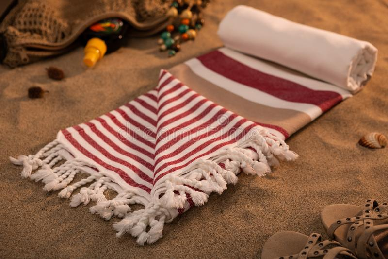 Handwoven hammam Turkish cotton towel on sandy beach. With crochet bag and sandals on the sides royalty free stock photo