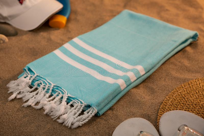 Handwoven hammam Turkish cotton towel on the sandy beach. With flip flops, baseball hat, sun lotion and pebbles on the side royalty free stock photos