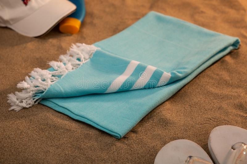 Handwoven hammam Turkish cotton towel on the sandy beach. With flip flops, baseball hat and sun lotion on the side royalty free stock photo