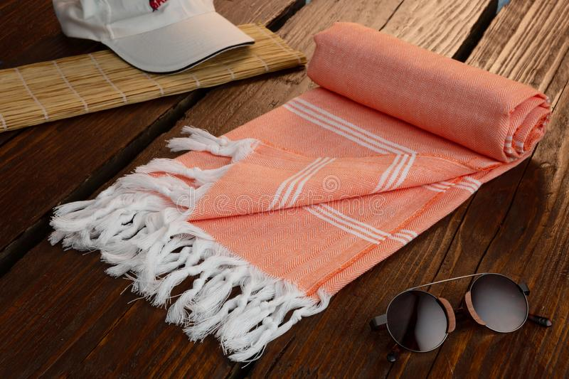 Orange Handwoven hammam Turkish cotton towel on wooden pier. Handwoven hammam Turkish cotton towel on wooden background stock photography