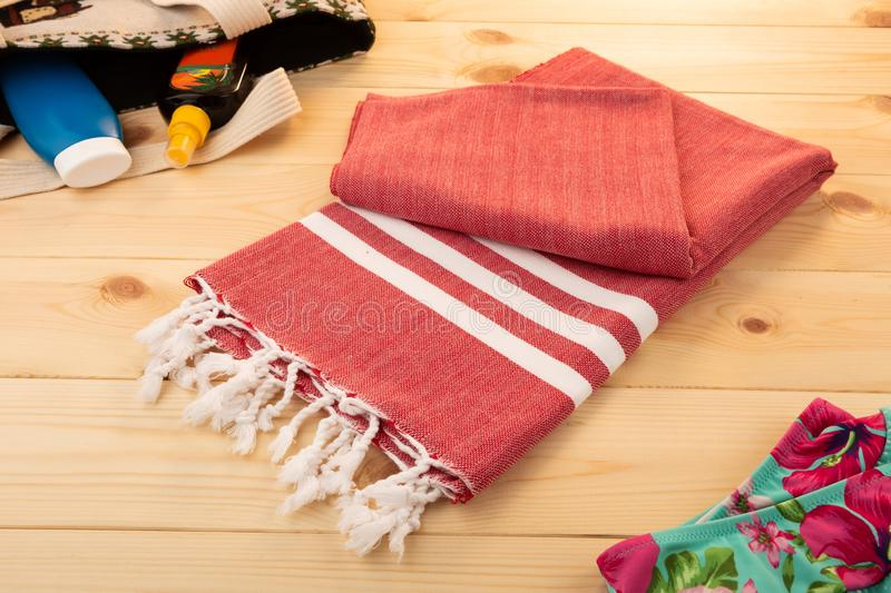 Handwoven red hammam Turkish cotton towel. On light wooden background with bikini, bag, and sun lotions on the side stock images