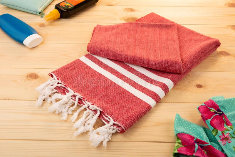 Handwoven red hammam Turkish cotton towel. On light wooden background with bikini, bag, and sun lotions on the side royalty free stock photos