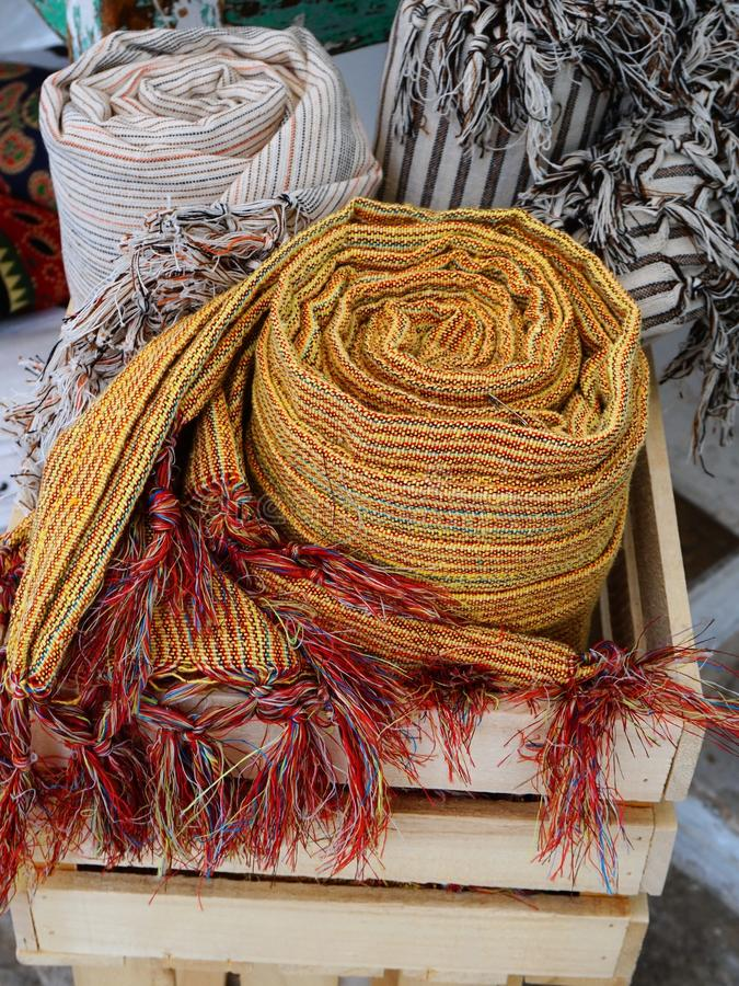 Handwoven Shawls. Several handwoven womens shawls, rolled up on display outside a craft shop, Tinos, Greek Island, Greece stock photography
