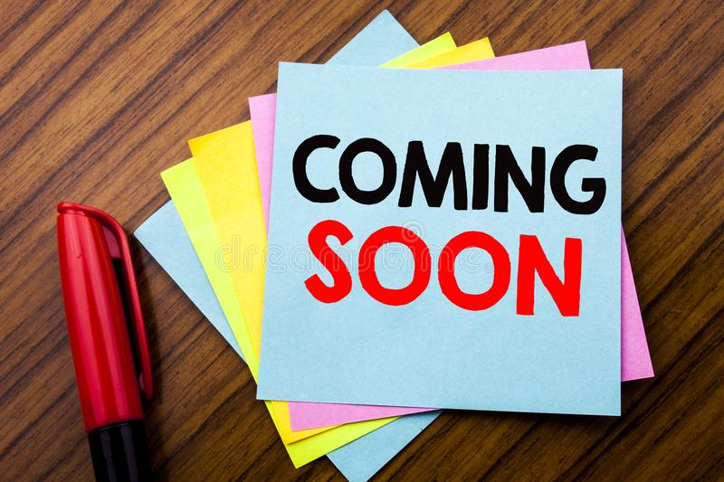 Handwriting Announcement text Coming Soon. Concept for Under Construction Written on sticky stick note paper with wooden backgrou. Handwriting Announcement text royalty free stock image