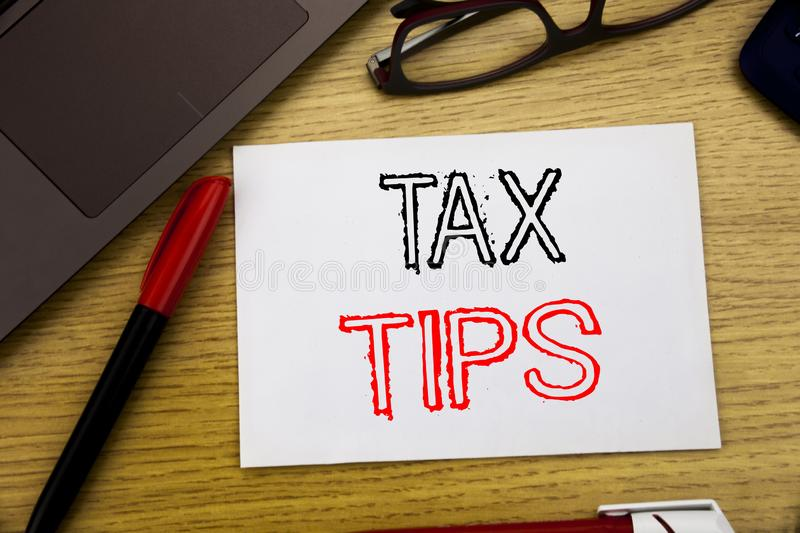 Handwriting Announcement text showing Tax Tips. Business concept for Taxpayer Assistance Refund Reimbursement written on paper, wo. Oden background in office stock images