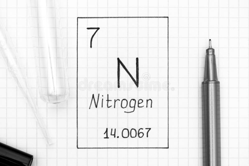 Handwriting chemical element Nitrogen N with black pen, test tub stock photos