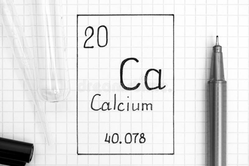 Handwriting chemicznego elementu wapnie Ca z czarnym piórem, próbną tubką i pipetą, zdjęcia royalty free
