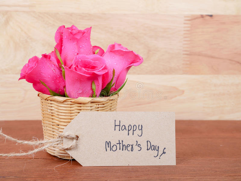 Handwriting Happy Mother`s Day and Carnation flower 3. Sweet pink rose flower in the basket and handwriting Happy Mother`s Day on brown label paper stock photo