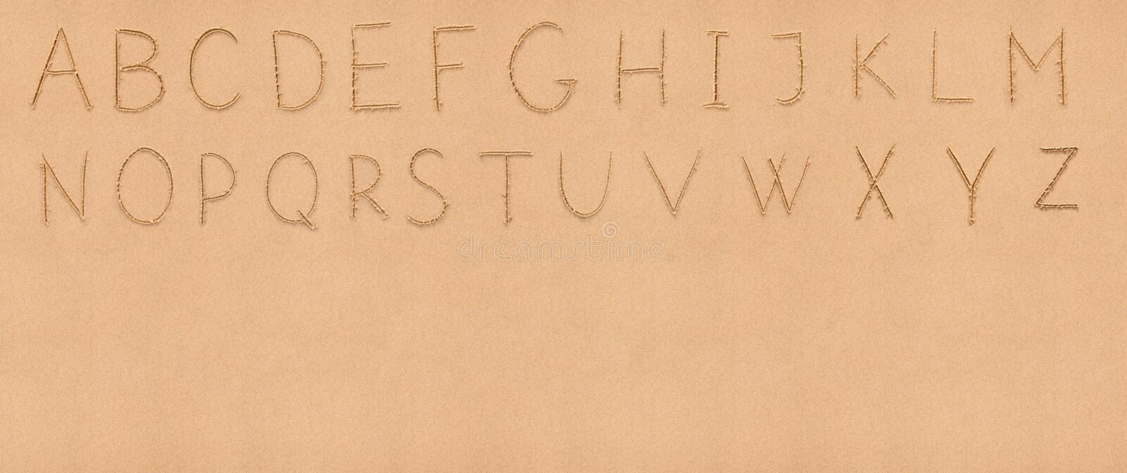 Handwriting latin alphabet on sand with. Handwriting English alphabet on flat sand with empty space appropriate as a background for your text royalty free stock images