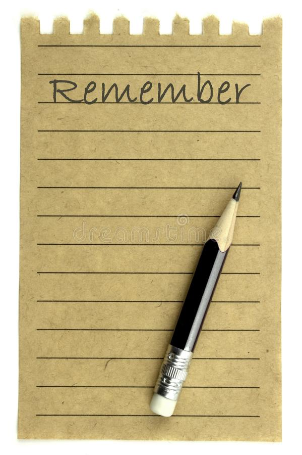 Handwriting Remember on a natural note paper and pencil royalty free stock images