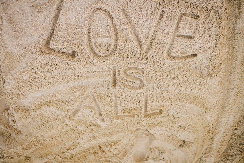 Handwriting słowa miłość SĄ WSZYSTKO na piasku plaża obraz royalty free