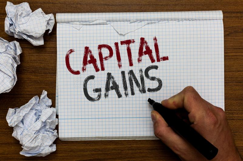 Handwriting text Capital Gains. Concept meaning Bonds Shares Stocks Profit Income Tax Investment Funds Man holding marker notebook. Crumpled papers ripped pages stock image