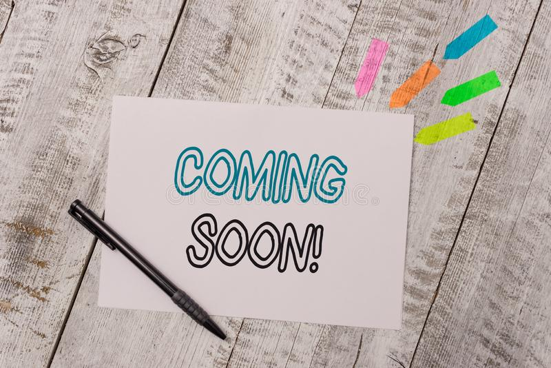 Handwriting text Coming Soon. Concept meaning event or action that will happen after really short time Plain note paper. Handwriting text Coming Soon. Conceptual stock photo