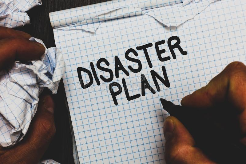 Handwriting text Disaster Plan. Concept meaning Respond to Emergency Preparedness Survival and First Aid Kit Man holding marker no. Tebook crumpled papers ripped royalty free stock images