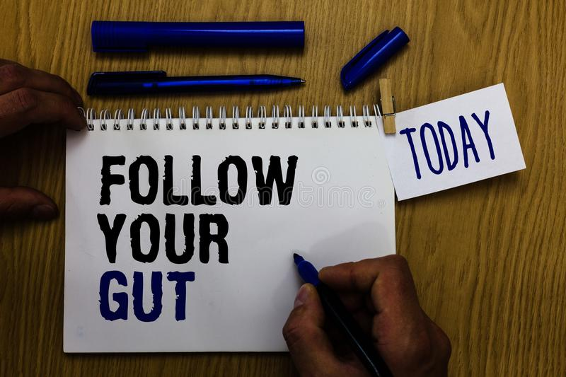 Handwriting text Follow Your Gut. Concept meaning Listen to intuition feelings emotions conscious perception Man holding marker no. Tebook clothespin reminder royalty free stock photo