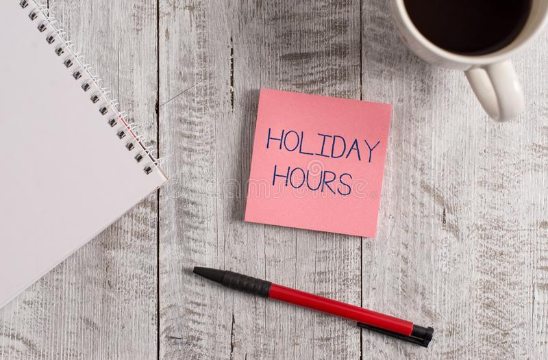 Handwriting text Holiday Hours. Concept meaning employee receives twice their normal pay for all hours Stationary placed. Handwriting text Holiday Hours stock photos