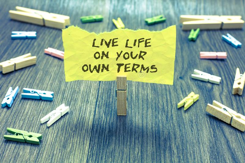 Handwriting text Live Life On Your Own Terms. Concept meaning Give yourself guidelines for a good living Paperclip hold written to. Rn page many clips laid on royalty free stock image