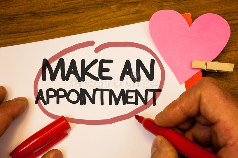 Handwriting text Make An Appointment. Concept meaning Schedule Arrangement Deadline Session Engagement Human hand retain red pen c. Ircled black words paper hook royalty free stock photo