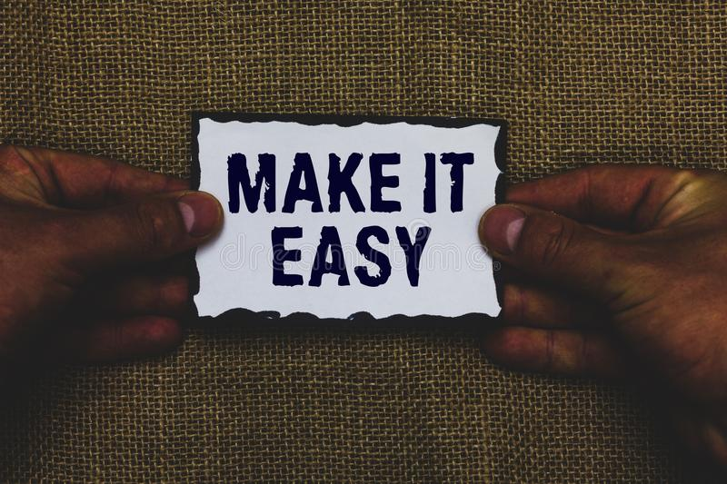 Handwriting text Make It Easy. Concept meaning Smart approach Effortless Free from worries or difficulties Man holding piece paper. Black borders jute royalty free stock photography
