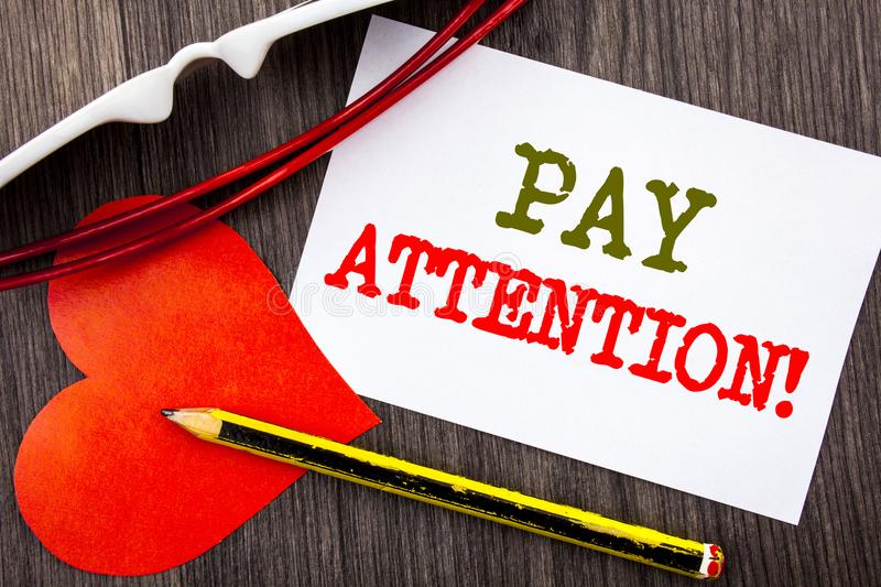 Handwriting text showing Pay Attention. Business concept for Be Careful Beware Mindful Alarm written on Sticky note paper with pen. Handwriting text showing Pay stock image