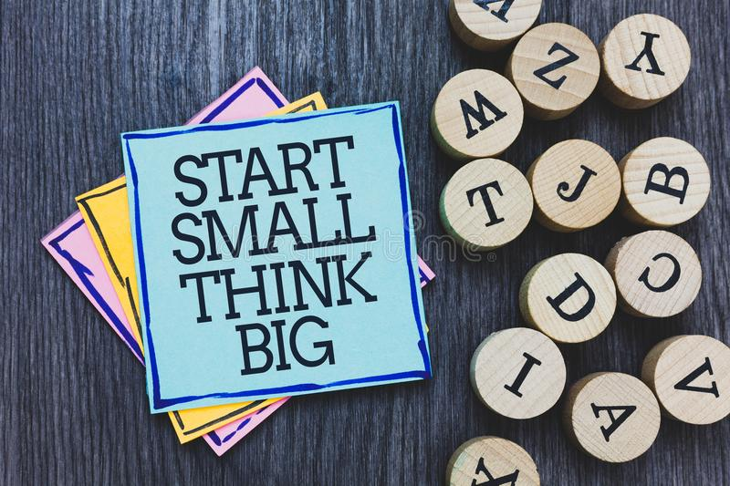 Handwriting text Start Small Think Big. Concept meaning Initiate with few things have something great in mind Black wooden deck wr. Itten sticky note beside some stock photos