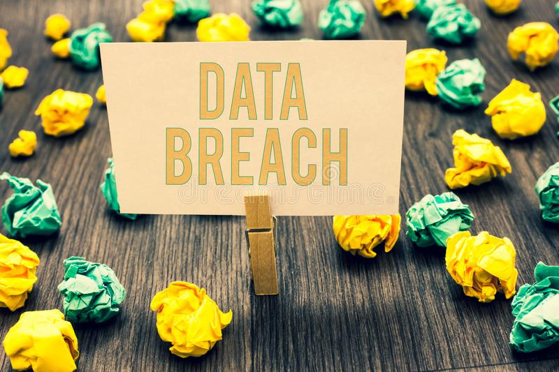 Handwriting text writing Data Breach. Concept meaning security incident where sensitive protected information copied Clothespin ho. Lding light pink note paper stock photography