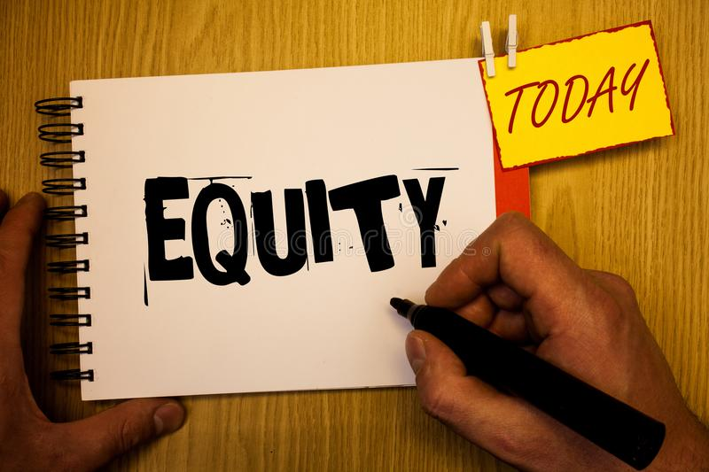 Handwriting text writing Equity. Concept meaning Value of a company divided into equal parts owned by shareholders Man hold holdin. G black marker notebook royalty free stock photos