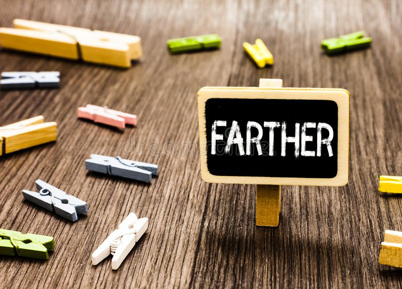 Handwriting text writing Farther. Concept meaning Greater distance More advanced point Comparative of far adverb. Blackboard standing several clothespins royalty free stock photography