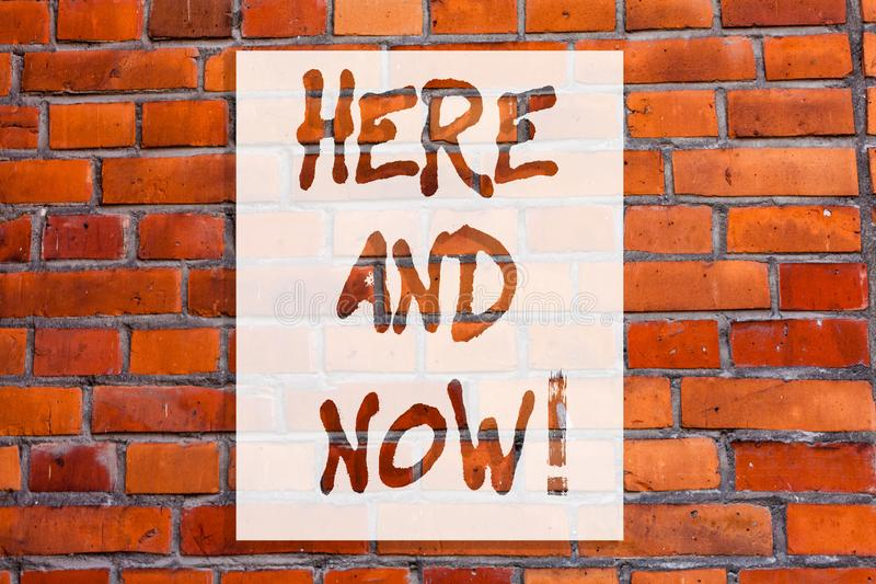 Handwriting text writing Here And Now. Concept meaning Present at this exact moment Compromise Engagement in situation. Brick Wall art like Graffiti royalty free stock images