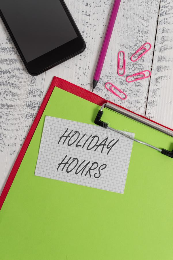 Handwriting text writing Holiday Hours. Concept meaning employee receives twice their normal pay for all hours Clipboard. Handwriting text writing Holiday Hours stock photo